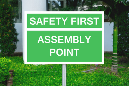 assembly point: Safety first and assembly point on green signpost Stock Photo