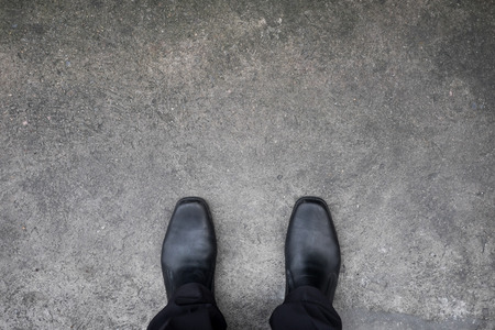 concrete steps: black shoes standing on the concrete floor