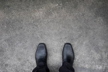 concrete: zapatos negros de pie en el suelo de cemento