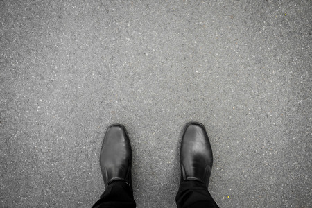 black shoes standing on the asphalt concrete floor