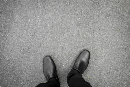 first floor: black shoes standing on the asphalt concrete floor