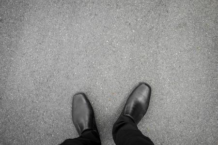 concrete: zapatos negros de pie en el piso de concreto asfáltico Foto de archivo
