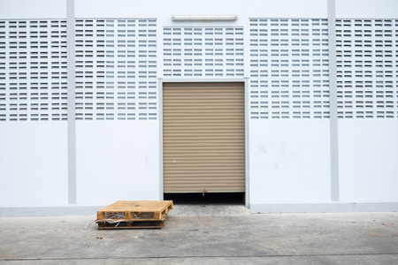 Roll garage gate on white concrete wall and old wooden pallet on concrete floor