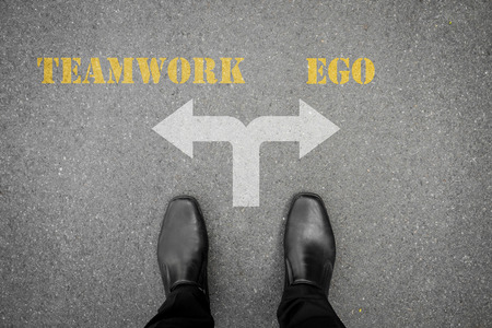 ego: Black shoes have decision to make at the cross road - teamwork or ego Stock Photo