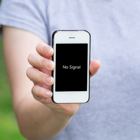 no signal: Woman in grey shirt show mobile phone with message No Signal on the screen Stock Photo