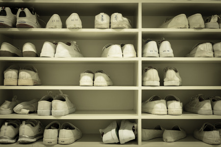 changing room: shoes rack in uniform changing room in factory or school Stock Photo