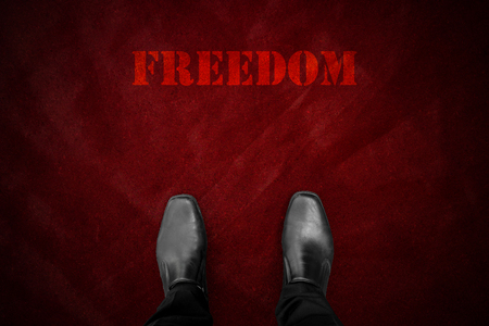 """uomo rosso: scarpe nere in piedi al tappeto rosso e la parola """"libert�"""" Archivio Fotografico"""