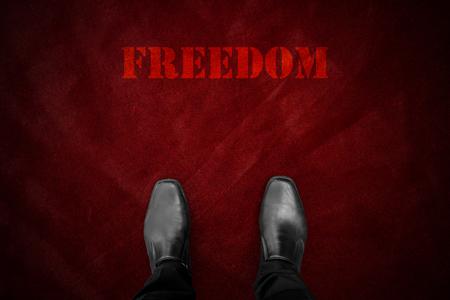 """hombre rojo: zapatos negros de pie en la alfombra y la palabra """"libertad"""" de color rojo"""