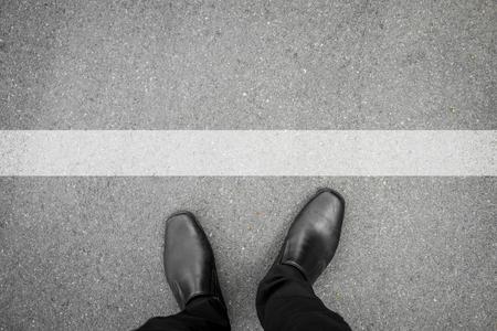 アスファルト コンクリートの床に白線の前に立っている黒い靴 写真素材