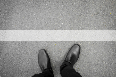 black shoes standing in front of white line on asphalt concrete floor