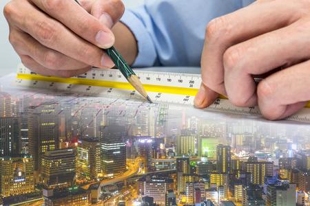 エンジニアは、鉛筆と定規の建物全体の世界を使用して図面に距離を測定します。