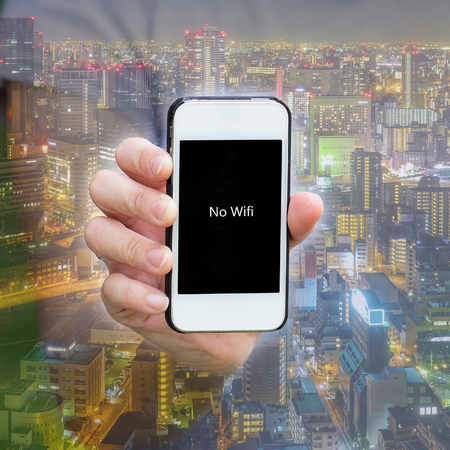 city scene: One show no wifi screen on smartphone in night cityscape background. Showing how important smart phone to the world today. Stock Photo