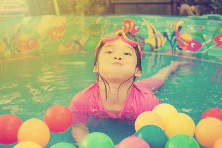 kiddie: A baby girl in pink suit playing water and balls in blue kiddie pool - vintage effect Stock Photo