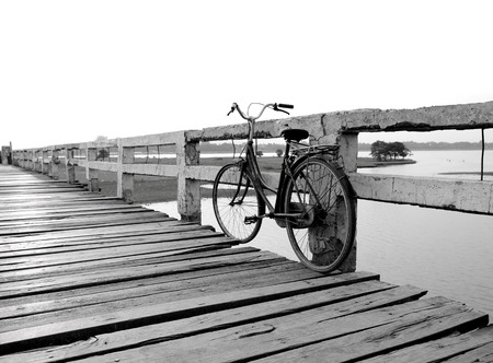 old metal: Black and white old bicycle on wooden bridge