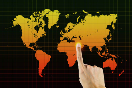 opec: Finger point to middle east on grid world map Stock Photo
