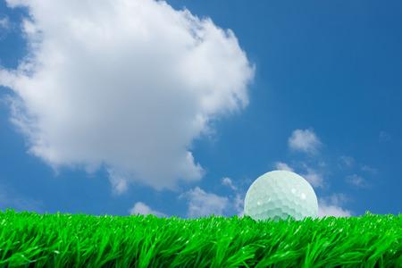 pelota de golf: Pelota de golf blanca en el c�sped artificial verde en fondo de cielo azul
