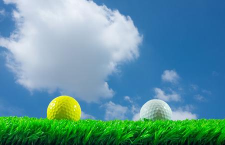 golf  ball: Pelotas de golf blancas y amarillas en el césped artificial verde en fondo de cielo azul Foto de archivo