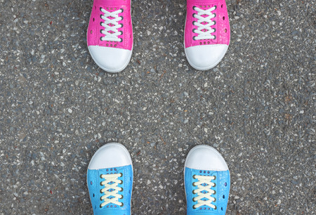 work shoes: Blue shoes and pink shoes standing on asphalt concrete floor