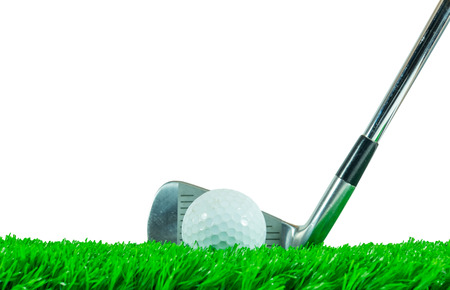 White golf ball and iron club on green artificial grass