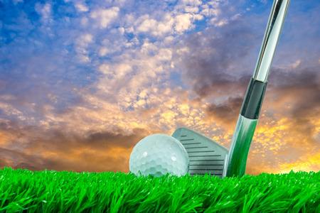 pelota de golf: Pelota de golf blanca y club del hierro en hierba verde artificial en el fondo del cielo por la noche