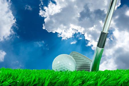 pelota de golf: Pelota de golf blanca y club del hierro en hierba verde artificial en el cielo azul de fondo de verano Foto de archivo