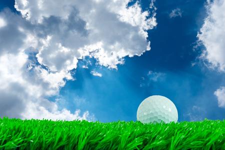 pelota de golf: White golf ball on green artificial grass in summer blue sky background