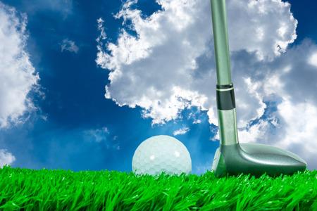 pelota de golf: White golf ball and fairway wood on green artificial grass and blue sky background Foto de archivo