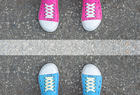 Blue shoes and pink shoes standing on asphalt concrete floor and white line between them Archivio Fotografico