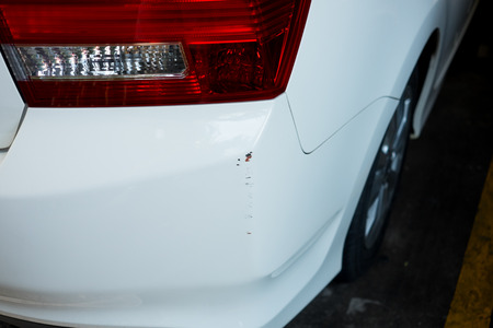dent: Small dent on white cars rear bumper Stock Photo