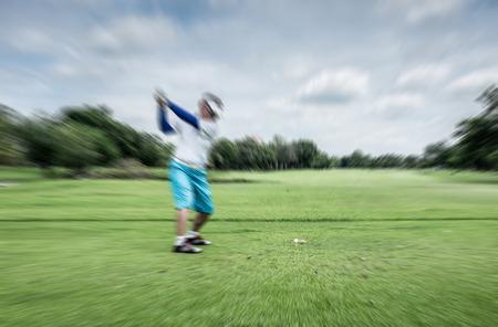golf swings: Motion blur golfer swinging driver club on teeing ground Stock Photo