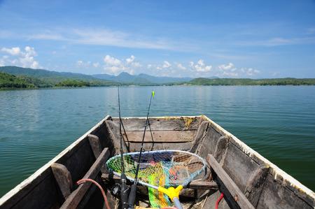 Barco de pesca de madera con la caña de pescar en dirección al lago Foto de archivo - 48513117
