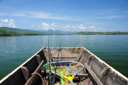 fishing lake: Wooden fishing boat with fishing rod heading to the lake Stock Photo