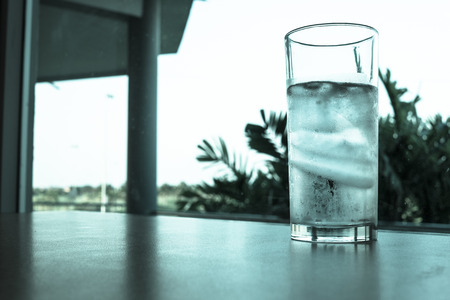 Glass of water and ice on the table - cold filter
