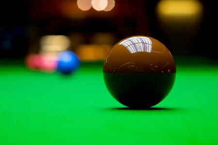 snooker balls: Snooker balls on green woolen fabric table - focus on brown ball