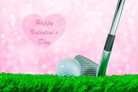 White golf ball and iron club on green artificial grass and beautiful off focus background and quote  Happy Valentines Day  Imagens