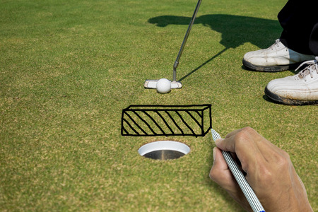 mind game: Hand writing wall between golf ball and hole, mind game of golfers
