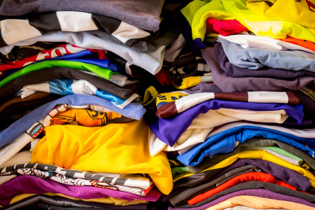 Messy folded colorful T-shirt stacking in the closet Imagens