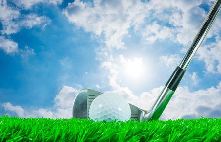 緑の人工芝とバック グラウンドで輝く太陽と青い空の曇りホワイト ゴルフ ボールと鉄クラブ 写真素材