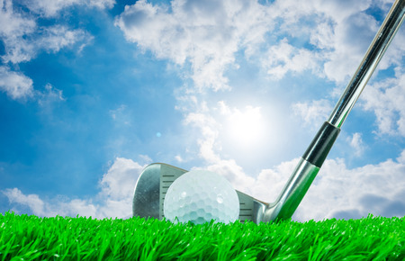 White golf ball and iron club on green artificial grass and cloudy blue sky with shining sun in the background