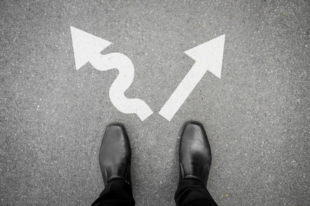 Chaussures noires debout à la croisée des chemins et doit prendre une décision où aller pour son succès - dure ou moyen facile