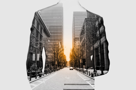 background project: Double exposure of businessman in suit and cityscape. Hes looking for his success in business and idea for life