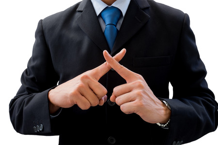 Businessman in dark gray suit using his hands as cross. Meaning wrong, fault, not correct, not allow, prohibit.