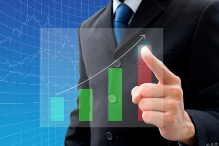 Businessman in dark gray suit pointing to the highest point of the bar chart
