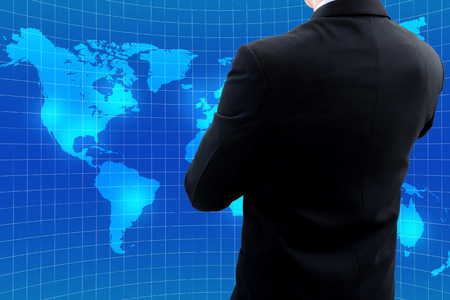 world thinking: Isolated back side of businessman in dark gray suit standing and crossing ones arm watching world map and thinking about global business