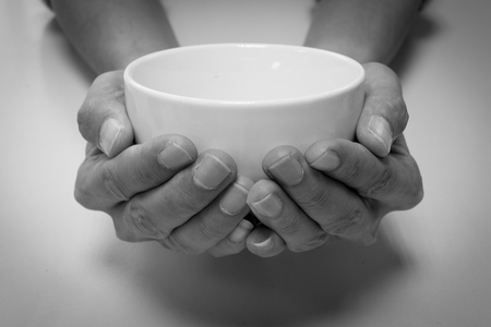 Hungry people begging for food with empty white bowl - black and white filter