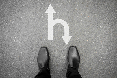 u turn sign: black shoes standing at the crossroad and has decision to make - move forward or u turn and go backward Stock Photo
