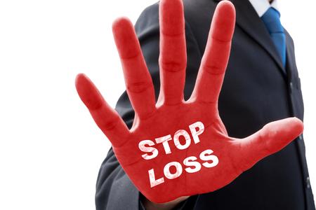 グレーのスーツのビジネスマンは、停止のアクションで手を挙げて、単語 'ストップロス' 自分の手のひらに
