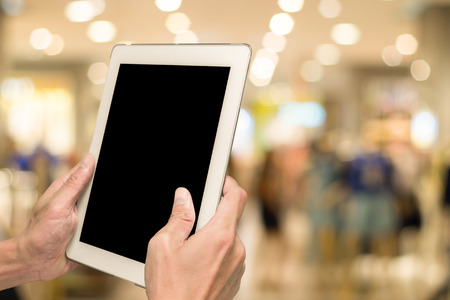 departmentstore: One using white tablet pc in shopping mall with bokeh background