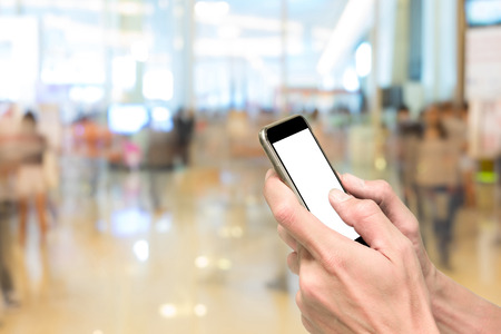 departmentstore: One using smartphone in front of exhibition hall with bokeh background Stock Photo