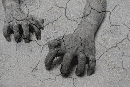 starvation: Double exposure of crawling hands and dry clay represent hungry people, poverty and starvation